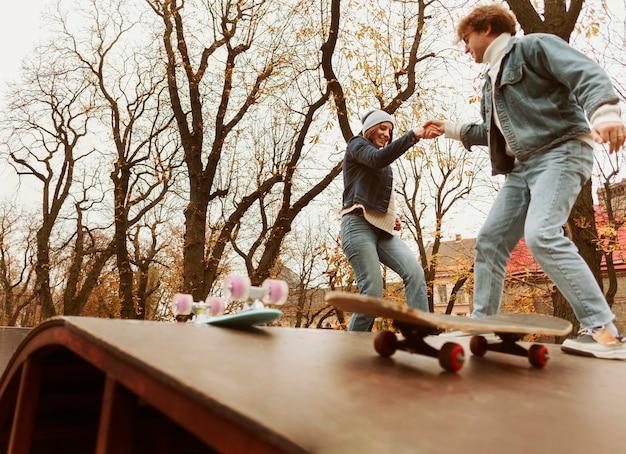 Uomo e donna che fanno skateboard all'aperto