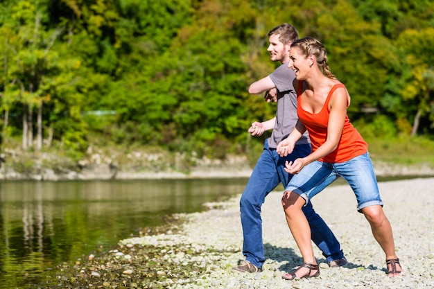 Man and woman skimming stones on river