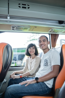 A man and a woman smile while sitting together in a bus seat while traveling