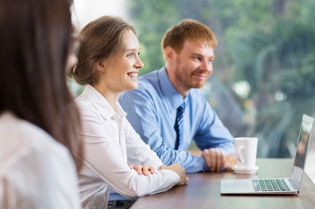L'uomo e la donna sorridente a un computer portatile