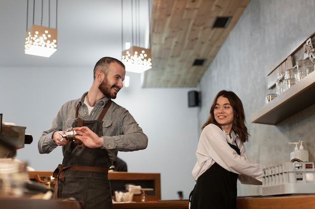 Man and woman smiling and working in coffee shop