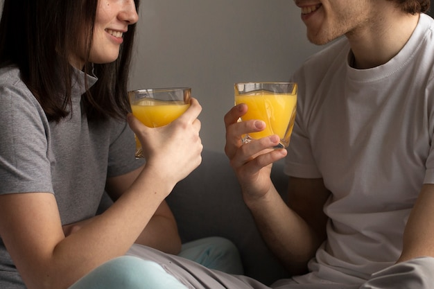 Man and woman smling and holding orange juice