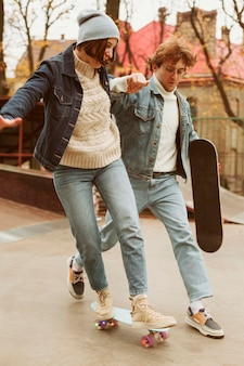 Man and woman spending time together outdoors with skateboards