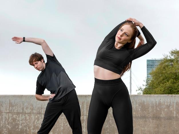 Uomo e donna in abiti sportivi che esercitano all'aperto