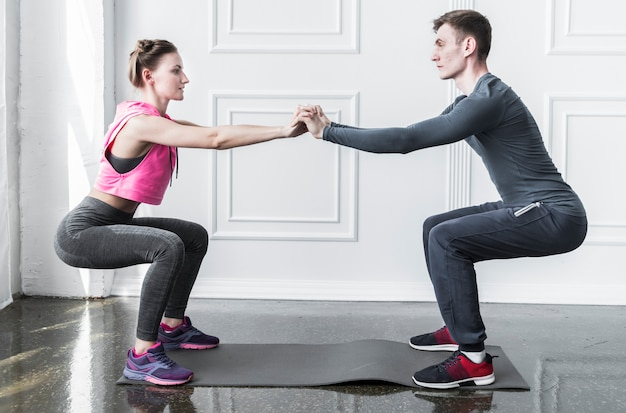 Man and woman squatting holding hands