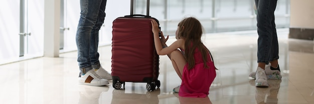 Man and woman stand at distance from each other in middle of child with a suitcase