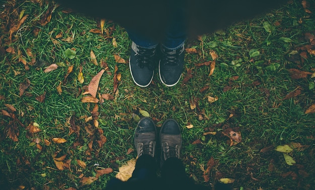 Man and woman stand opposite each other. close up of feet in winter boots in the autumn lawn