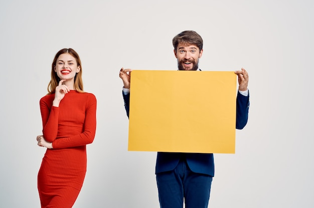 Man and woman standing next to advertising posing discount