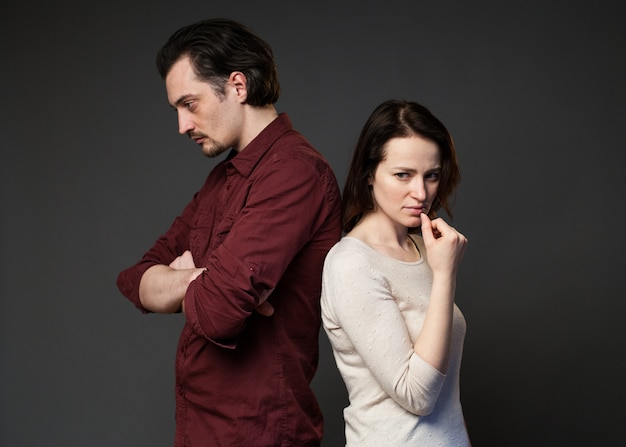 Man and woman standing back to each other