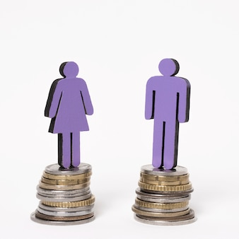 Man and woman standing on equal piles of coins