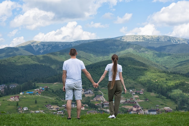 Man and woman standing on the hill and admire the view of the mountains. back view