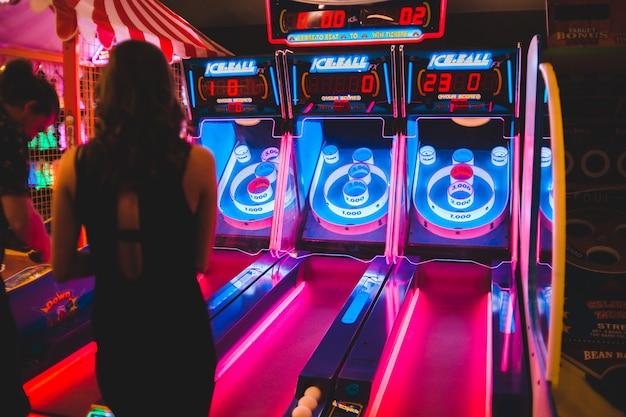 Uomo e donna che stanno vicino alla macchina arcade durante la notte
