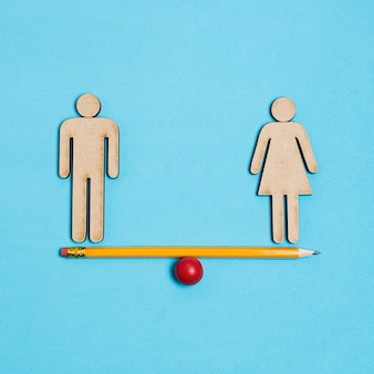 Man and woman standing on seesaw in balance