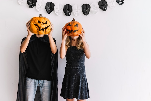 Man and woman standing with pumpkin faces