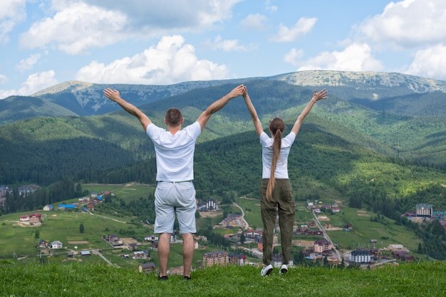 Man and woman standing with their hands up against a background of mountains. back view