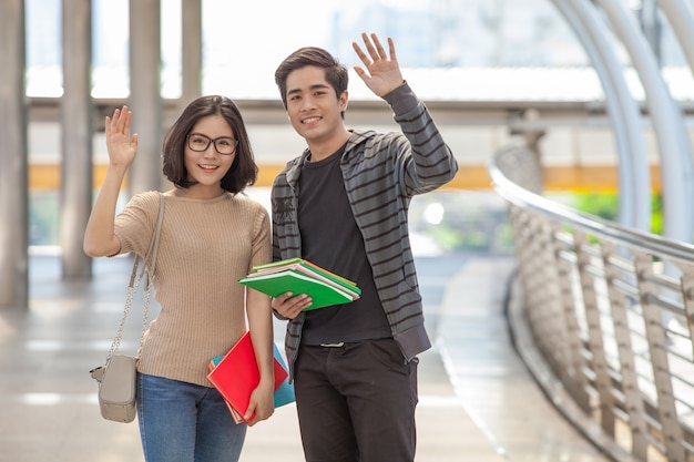 Man and woman students holding many books waving hands say hello to their friends