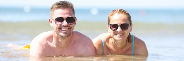 Man and woman in sunglasses lie in sea near shore.