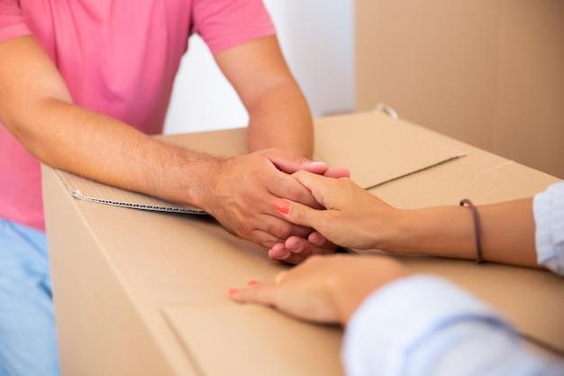 Uomo e donna si sostengono a vicenda e si tengono per mano su un pacco di cartone, mentre si trasferiscono nel nuovo appartamento