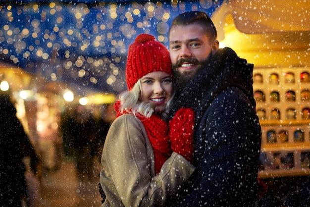 Uomo e donna circondati da fiocchi di neve