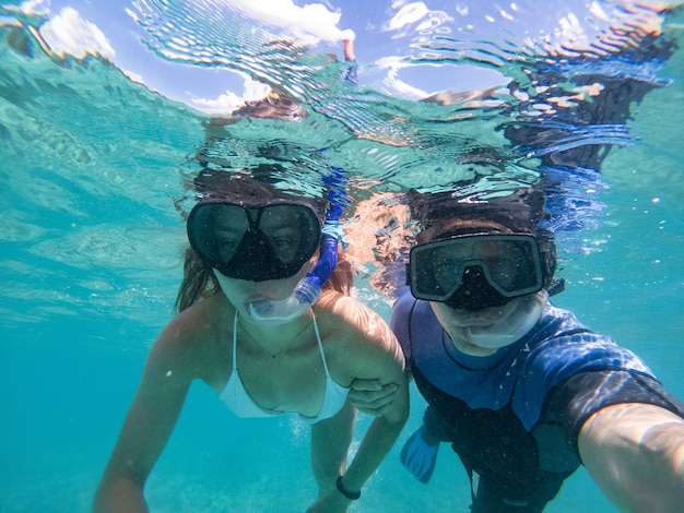 Man and woman swimming with snorkeling mask. concept about vacations, snorkeling and nature.