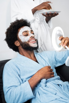 Man and woman taking care of their face at home