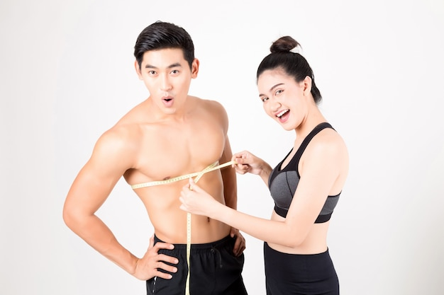 The man and woman taking measurements of them body