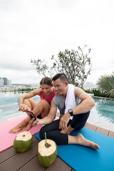 Man and woman taking picture of coconuts after yoga training