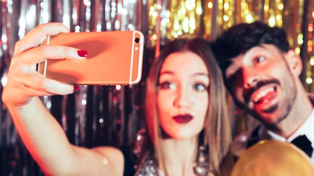 Uomo e donna che prendono selfie su partiti nuovi anni