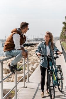 Uomo e donna che parlano accanto a una bici