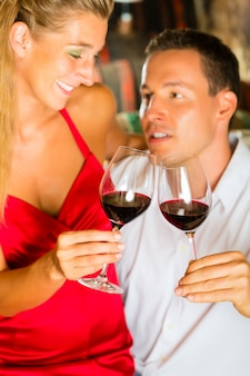 Man and woman tasking wine in cellar