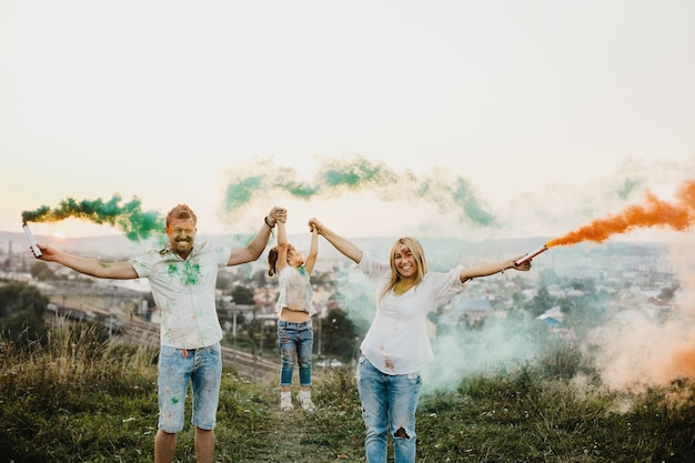 Man, woman and their little daughter have fun running with colorful smoke in their arms