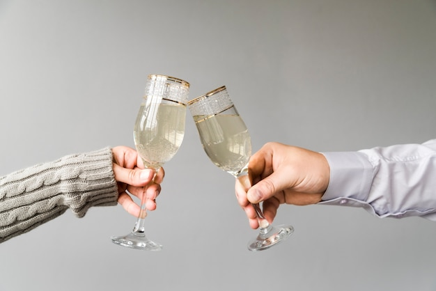 Man and woman toasting champagne flute over grey backdrop