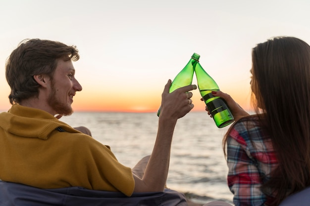 Man and woman toasting with beer bottles at sunset