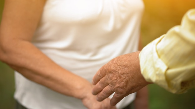 A man and a woman touching hands in the garden