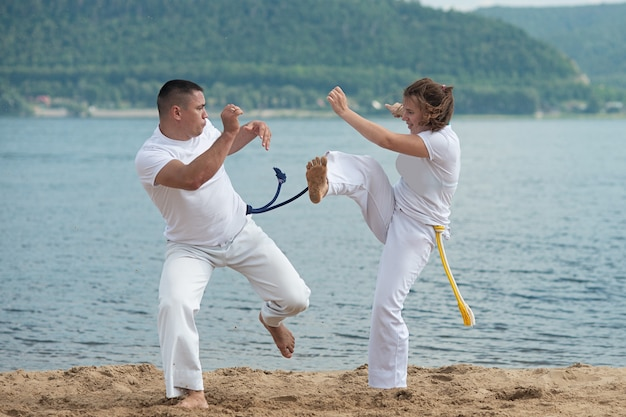 Man and woman train capoeira on the beach - concept about people, lifestyle and sport.