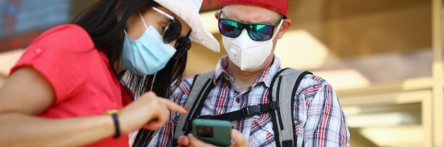 Man and woman at train station in protective medical masks are looking into smartphon