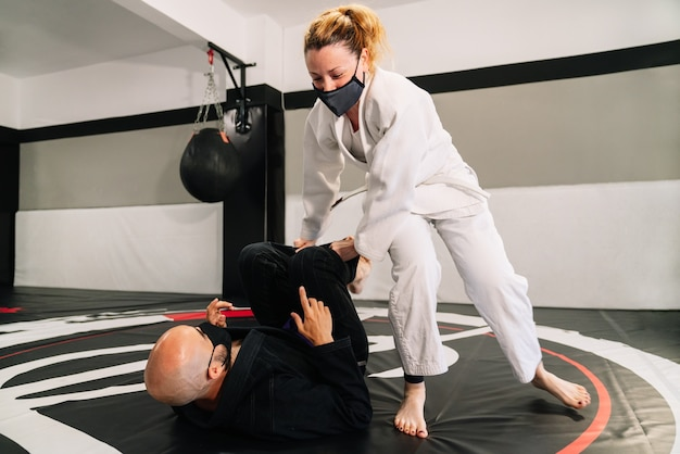 Man and woman training martial arts and judo with kimonos on the gym floor mat with a face mask because of the covid 19