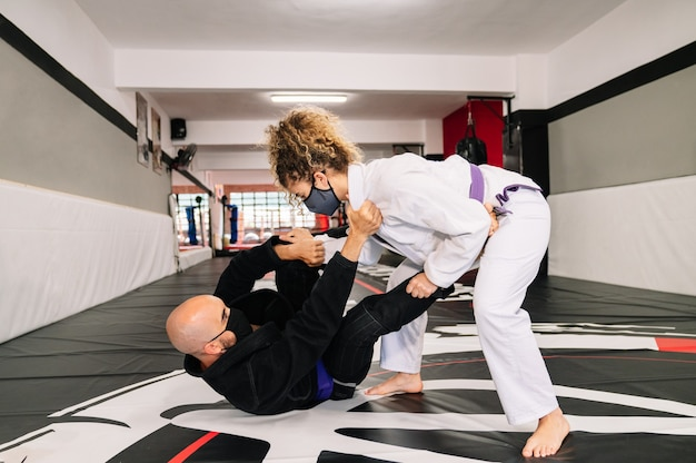Man and woman training martial arts with kimonos on the gym floor mat with a face mask because of the covid 19