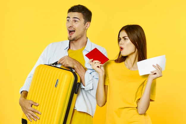 Man and woman traveler with a suitcase, colored background, joy, passport