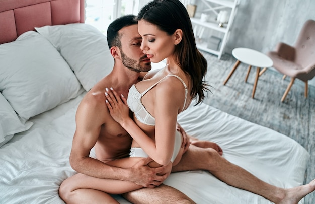 The man and woman in underwear having sex in the bed