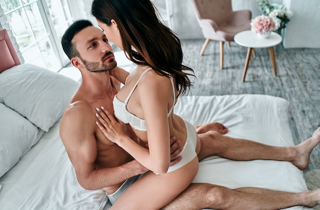 The man and woman in underwear sitting on the bed