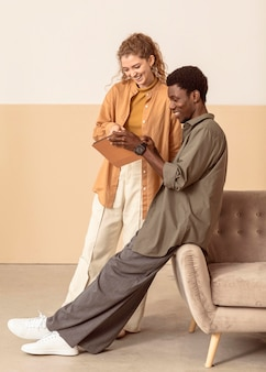 Uomo e donna che utilizzano una vista lunga della tavoletta digitale