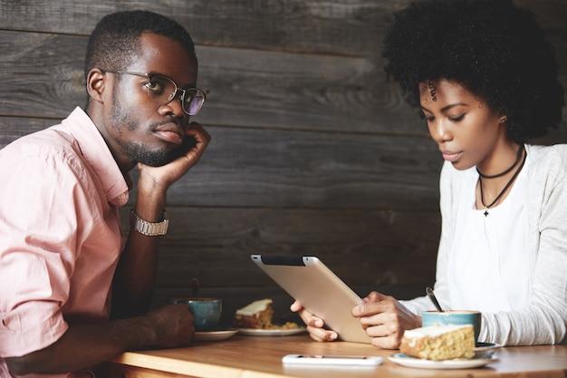 Uomo e donna che utilizza tablet nella caffetteria