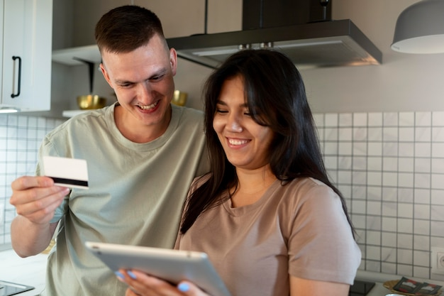 Man and woman using tablet for online shopping with credit card