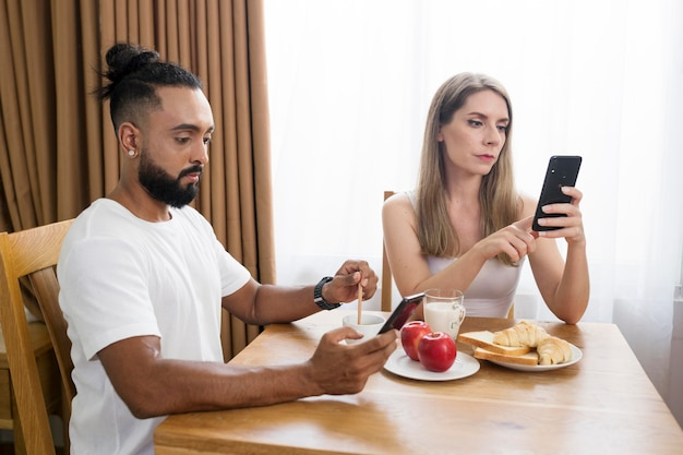 Uomo e donna che usano il telefono in cucina