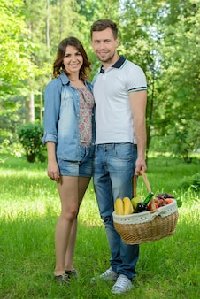 Man and woman walk on picnic in park.