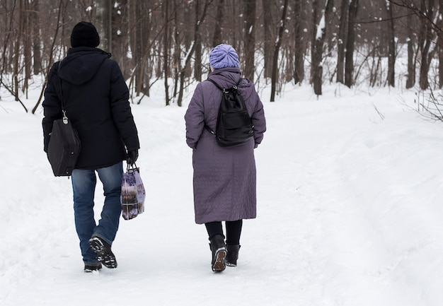 A man and a woman walk through a winter park ,talking sweetly to each other.