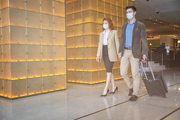 Man and woman walking in the airport hall with medical masks on their faces. template banner