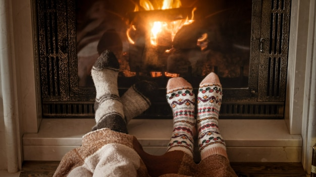 Man and woman warming and relaxing by the fireplace at cold day
