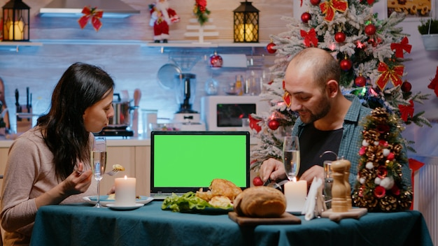 Man and woman watching green screen on laptop